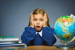 Concepto de la escuela muchacha con la expresión asombroso o de la duda que se sienta en el escritorio Fotografía de archivo libre de regalías
