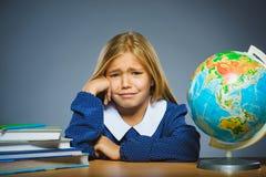 Concepto de la escuela muchacha gritadora con la expresión asombroso o de la duda que se sienta en el escritorio Fotos de archivo libres de regalías