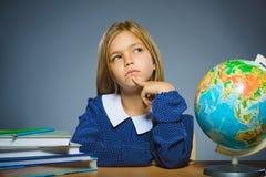 Concepto de la escuela muchacha que piensa o que se sienta en el escritorio en la geografía de la sala de clase Imagen de archivo