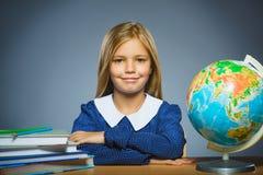 Concepto de la escuela muchacha que se sienta en el escritorio en la geografía de la sala de clase Fotografía de archivo