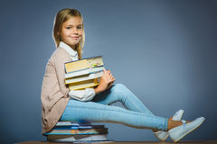 Concepto de la escuela muchacha que se sienta en los libros y que sostiene un libro disponible Foto de archivo