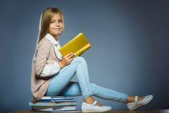 Concepto de la escuela muchacha que se sienta en los libros y que sostiene un libro disponible Imagen de archivo