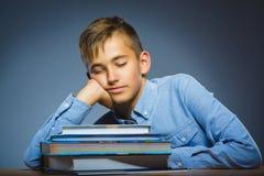 Concepto de la escuela Muchacho del retrato del primer dormido en la pila de libros Imágenes de archivo libres de regalías