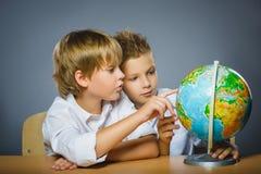 Concepto de la escuela Muchachos felices sonrientes que se sientan en el escritorio y la demostración en el globo Fotos de archivo