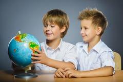 Concepto de la escuela Muchachos felices sonrientes que se sientan en el escritorio y la demostración en el globo Fotografía de archivo libre de regalías
