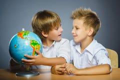 Concepto de la escuela Muchachos felices sonrientes que se sientan en el escritorio y la demostración en el globo Fotografía de archivo