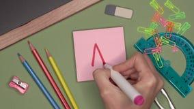 Concepto de la escuela Mujer que escribe a A con la marca menos en la libreta pegajosa almacen de metraje de vídeo