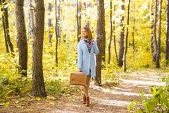 Concepto de la estación, de la naturaleza y de la gente - mujer en el parque del otoño que se coloca con la maleta foto de archivo