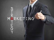 Concepto de la estrategia de marketing de la escritura del hombre de negocios Imágenes de archivo libres de regalías