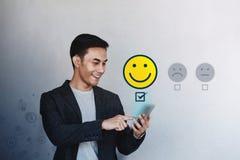 Concepto de la experiencia del cliente Hombre de negocios joven Giving su estudio positivo en encuesta sobre en l?nea la satisfac fotografía de archivo libre de regalías