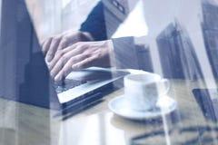 Concepto de la exposición doble Hombre de negocios adulto que trabaja en la tabla de madera en oficina moderna Hombre que usa el  Fotos de archivo libres de regalías
