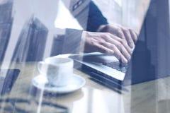 Concepto de la exposición doble Hombre de negocios adulto que trabaja en la tabla de madera en oficina moderna Hombre que usa el  Imagen de archivo