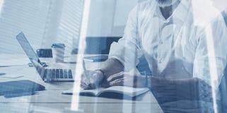 Concepto de la exposición doble Hombre de negocios barbudo adulto que trabaja con el ordenador portátil en la tabla de madera en  Imagen de archivo libre de regalías