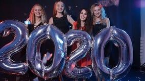 Concepto de la Feliz Año Nuevo El grupo de mujeres jovenes se está divirtiendo y está llevando a cabo números más grandes 2020 metrajes