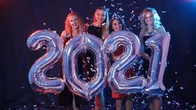 Concepto de la Feliz Año Nuevo El grupo de mujeres jovenes se está divirtiendo y está llevando a cabo números más grandes 2021 metrajes