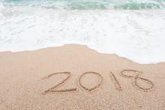 Concepto 2018 de la Feliz Año Nuevo Número 2018 escrito en la playa arenosa Fotografía de archivo