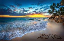 Concepto 2018 de la Feliz Año Nuevo, poniendo letras en la playa Salida del sol del mar Imagenes de archivo