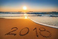 Concepto 2018 de la Feliz Año Nuevo, poniendo letras en la playa Salida del sol del mar Fotografía de archivo