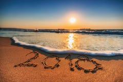 Concepto 2018 de la Feliz Año Nuevo, poniendo letras en la playa Salida del sol del mar Imágenes de archivo libres de regalías