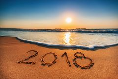 Concepto 2018 de la Feliz Año Nuevo, poniendo letras en la playa Salida del sol del mar Foto de archivo libre de regalías