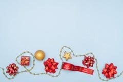 Concepto de la Feliz Navidad, cajas de regalos o cajas de los presentes con los arcos, la estrella y la bola rojos en fondo azul fotos de archivo
