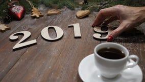 Concepto de la Feliz Navidad y de la Feliz Año Nuevo 2019 símbolos de madera y taza de café colocados en fondo con el árbol de ab metrajes