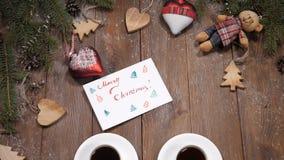 Concepto de la Feliz Navidad y de la Feliz Año Nuevo Tazas de café colocadas en fondo de madera así como ramas de árbol de abeto metrajes