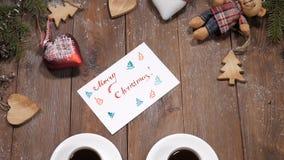 Concepto de la Feliz Navidad y de la Feliz Año Nuevo Tazas de café colocadas en fondo de madera así como ramas de árbol de abeto almacen de metraje de vídeo