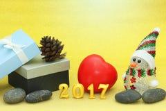 Concepto 2017 de la feliz Navidad y de la Feliz Año Nuevo adornado con el muñeco de nieve, caja de regalo, pino del cono, rocas,  Imagen de archivo