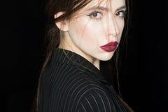 Concepto de la feminidad Muchacha en cara confiada estricta en la chaqueta negra, fondo negro Mujer con maquillaje elegante y imágenes de archivo libres de regalías