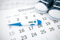 Concepto de la fertilidad con el termómetro en calendario Fotografía de archivo libre de regalías
