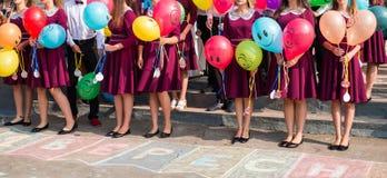 Concepto de la forma de vida - los diplomados de High School secundaria sostienen los globos en sus manos fotografía de archivo libre de regalías