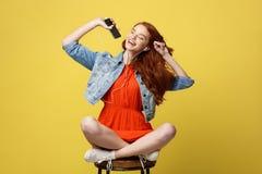 Concepto de la forma de vida - mujer bastante roja feliz del pelo en auriculares que escucha la música y que canta mientras que s Imagen de archivo libre de regalías