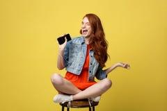 Concepto de la forma de vida - mujer bastante roja feliz del pelo en auriculares que escucha la música y que canta mientras que s Imagen de archivo