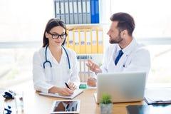 Concepto de la formación de equipo Dos trabajadores del médico en las capas blancas son disco imagenes de archivo