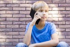 Concepto de la gente, de la tecnología y de la comunicación Niño que habla en el teléfono celular Imágenes de archivo libres de regalías