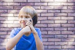 Concepto de la gente, de la tecnología y de la comunicación Niño que habla en el teléfono celular Foto de archivo