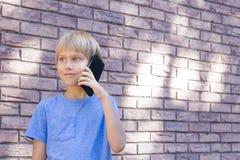 Concepto de la gente, de la tecnología y de la comunicación Niño que habla en el teléfono celular Imagen de archivo libre de regalías