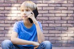 Concepto de la gente, de la tecnología y de la comunicación Niño que habla en el teléfono celular Fotos de archivo libres de regalías