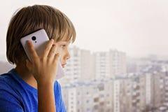 Concepto de la gente, de la tecnología y de la comunicación Niño que habla en el teléfono celular Fotografía de archivo libre de regalías