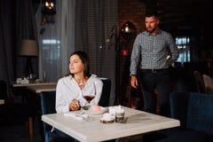 Concepto de la gente, de la sorpresa y de la datación - vino de consumición de los pares felices en el café o el restaurante fotografía de archivo