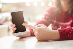 Concepto de la gente, de la tecnología y de la publicidad La hembra sostiene el teléfono celular, lo indica en la pantalla en bla foto de archivo