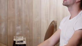Concepto de la gente, de la tostada, del ocio, de la amistad y de la celebración - amigos masculinos felices que beben la cerveza almacen de video