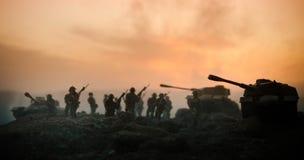 Concepto de la guerra Siluetas militares que luchan escena en el fondo del cielo de la niebla de la guerra, siluetas de los solda fotos de archivo