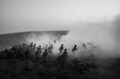 Concepto de la guerra Siluetas militares que luchan escena en el fondo del cielo de la niebla de la guerra, siluetas de los solda imágenes de archivo libres de regalías