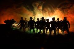 Concepto de la guerra Siluetas militares que luchan escena en el fondo del cielo de la niebla de la guerra, siluetas de los solda imagenes de archivo