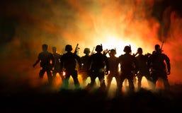 Concepto de la guerra Siluetas militares que luchan escena en el fondo del cielo de la niebla de la guerra, siluetas de los solda imagen de archivo