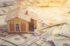 Concepto de la hipoteca Casa y dinero Modelo miniatura de la casa en pila Fotografía de archivo libre de regalías