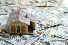Concepto de la hipoteca Casa y dinero Modelo miniatura de la casa en pila Imagenes de archivo