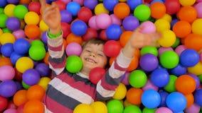 Concepto de la hospitalidad Fondo moderno del lifesyle Muchacho que miente en la piscina con las bolas suaves coloridas que agita almacen de video